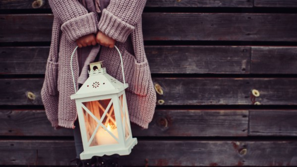 Photo credit: Daiga Ellaby: femme person in chunky neutral sweater, holding a white lamp with yellow-orange light.