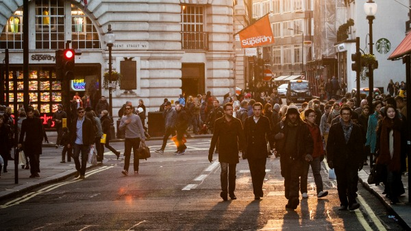 Street shot of Regent Street, London: small clusters of people of different genders walk along the edges of the street.