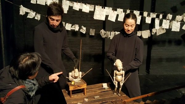 Two Silencio Blanco cast members in all-black demonstrate puppets. The puppets are white with coal dust over them. They sit or stand on a wooden prop. An audience member with face turned away from the camera points at one of the puppets. The cast member on the left looks down at him.