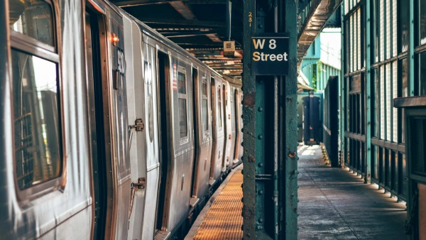 A platform view of Brooklyn's W 8th Street subway station. A train is on the left half of the photo; the green pillar with the white-on-black sign; and the platform to the right. It is daytime.