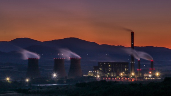 At sunset, a purple-orange sky hangs over several large smokestcks and a lit industrial complex. Smoke billows left from them all..