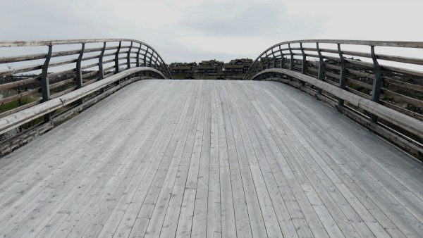 A wooden footbridge on a very grey day.
