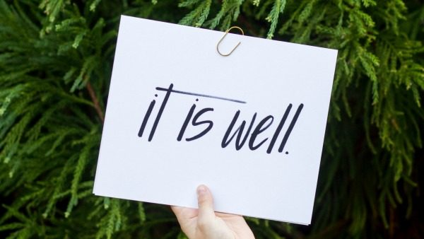 "A white hand holds a handwritten sign on white paper: ""It is well"" in lowercase print. In the background are deep green fir trees."