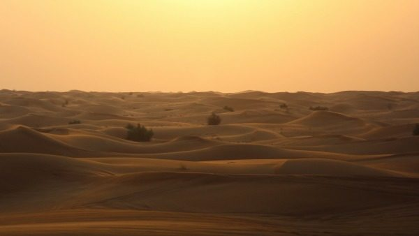 Deserted desert: light sands under an orange, yellow, and pastel sky. No people.