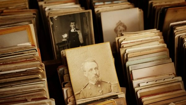 Boxes of stacked sepia classic photographs, in rows of three. A uniformed white man is in the center image. Above and to his right are women.