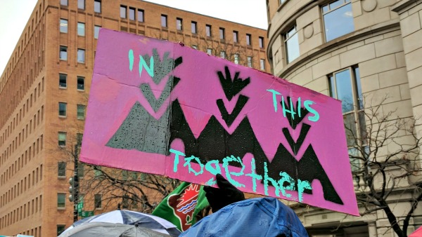 "A spray-painted sign: ""In this together"""
