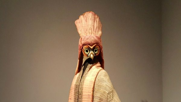 A beige and red-toned fabric cape and headpiece by Chickasaw designer Margaret Roach Wheeler. The headpiece has a beak and a long nape.
