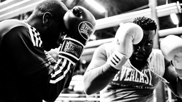 Black and white photo of two dark-skinned Black men sparring with boxing gloves raised.