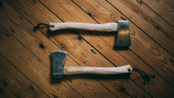 Two wooden-handled axes lie blade up and down, facing each other and forming a rectangle.