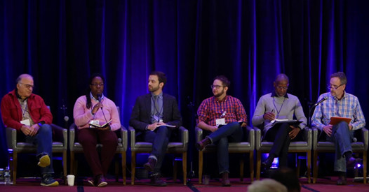 Screenshot of Dr. Keisha E. McKenzie at Rolling The Stone Away (2017) with Revs. Alex McNeill, Cedric Harmon, Ray Bagnuolo, Dr. Bernie Schlager, and Matthew Vines. All sit in a row-panel wearing sweaters, shirts, and pants. The background is a dark purple curtain. Dominant colors are dark blue, red, black, and Keisha's sweater, pink.